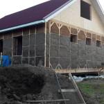 Вид дома с первым слоем глиняной штукатурки.
